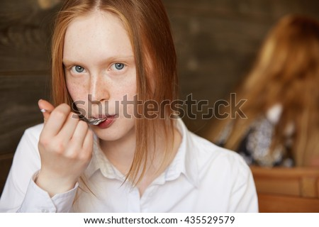 Close up shot of teenager eating dessert with a spoon, looking at the camera. Young Caucasian student girl with red hair and freckles wearing white shirt, enjoying delicious cake during lunch break - stock photo