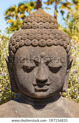 close up shot of the head of a buddhist statue in an ornamental garden - stock photo