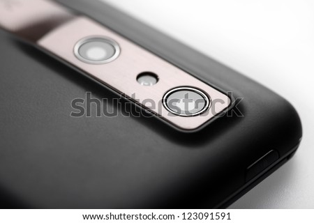 Close-up shot of the photo camera on the back of a mobile phone. - stock photo