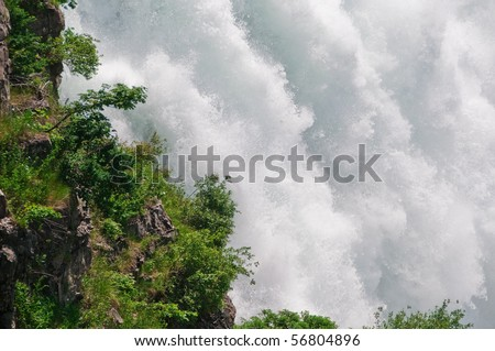 Close up shot of the water falling at Niagara Falls State Park in New York, USA, showing the power and strength of the water as it roars down the rocks into the Niagara river below. - stock photo