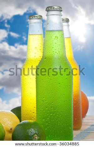 Close up shot of three bottles with tropical drink on wooden table - stock photo