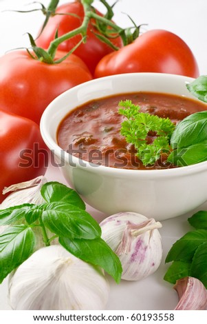 Close-up shot of tomato soup in bowl, set with garlic, tomatoes and basil - stock photo