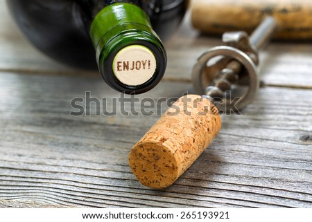 Close up shot of top of wine bottle cork, focus on the words enjoy, with rustic opener in background. Horizontal format layout.  - stock photo