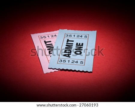 Close up shot of two generic admission tickets over red background. - stock photo