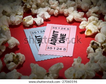 Close up shot of two generic admission tickets surrounded by popcorns. - stock photo