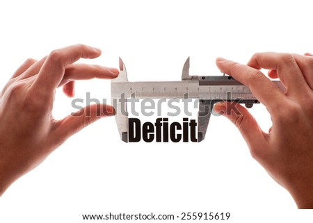 "Close up shot of two hands holding a caliper measuring the word ""Deficit"" - stock photo"