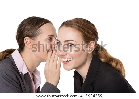 Close up shot of two happy, pretty business women, sharing a secret and whispering in each others ear.  Isolated on a white background - stock photo