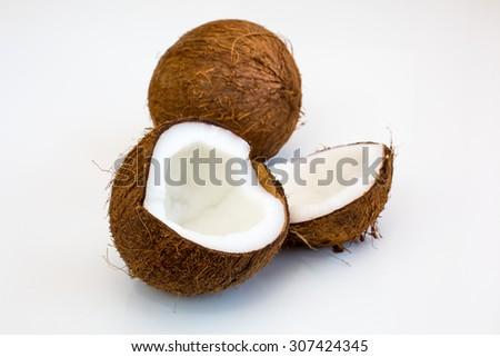 Close up shot of two parts of ripe brown fresh coconut and whole fruit on the white background