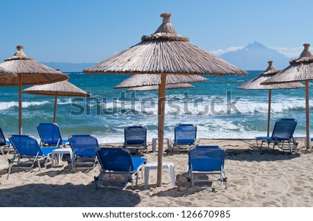 Close up shot of umbrella on the sandy beach with sea waves in the background - stock photo