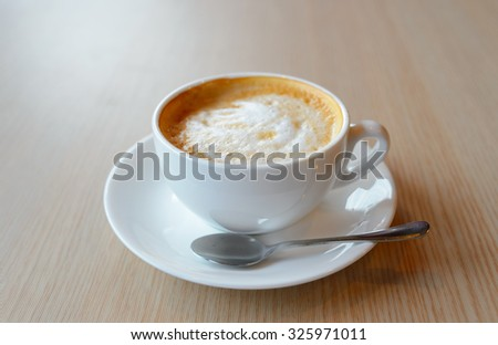 Close-up shot of white cup with hot latte on the table