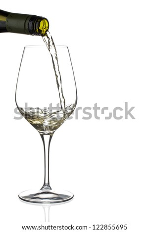 Close-up shot of wine bottle pouring wine in wineglass against white background. - stock photo