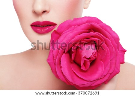Close-up shot of woman's lips with fuchsia lipstick and beautiful hot pink rose over white background