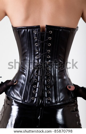 Close-up shot of woman wearing professional waist training black leather corset