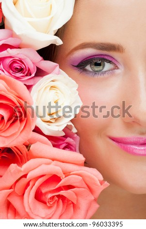 Close-up shot of woman with beautiful makeup and roses smiling and looking at camera