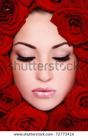 Close-up shot of young beautiful woman face with red roses around - stock photo