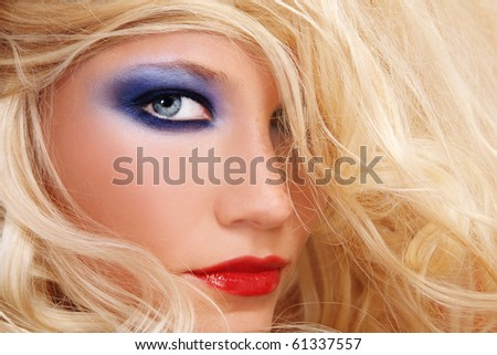 Close-up shot of young beautiful woman with long blond hair and stylish make-up - stock photo