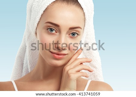 Close up shot of young Caucasian female with blue eyes and fresh healthy skin with no makeup, looking at the camera with beautiful smile while getting facial treatment in spa salon. Beauty concept  - stock photo