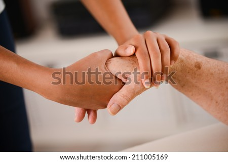 close-up shot of young person hands holding tenderly the hand of an elderly person - stock photo