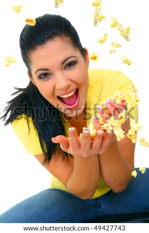 close up shot of young woman excited and throwing popcorn up in the air - stock photo
