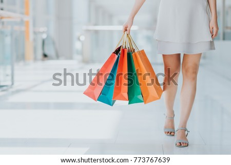 Close up shot of young woman leg carrying colorful shopping bags while walking in shopping mall