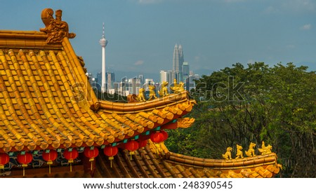 Close up shot on chinese temple roof with a view of Kuala Lumpur city. - stock photo