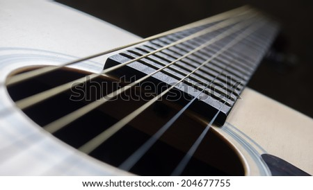Close up shot sound hole and strings of acoustic guitar - stock photo