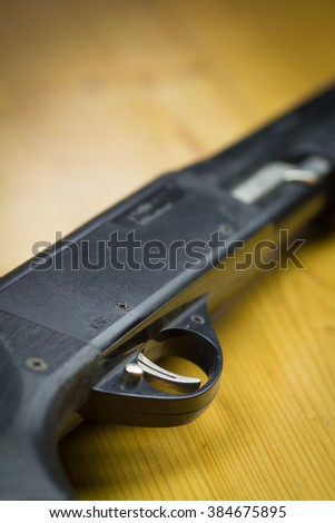 Close-up shotgun or gun on the old wood table (focus on trigger, shallow DOF) - stock photo