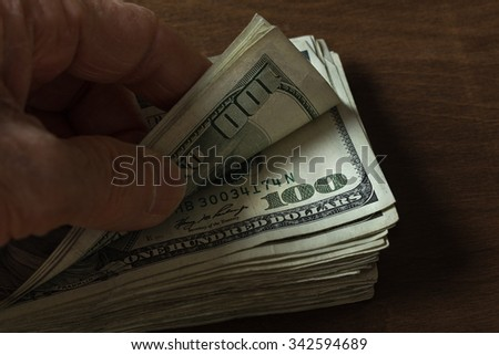 Close-up showing pile of $100 bills with thumb and fingers fliping through the stack.