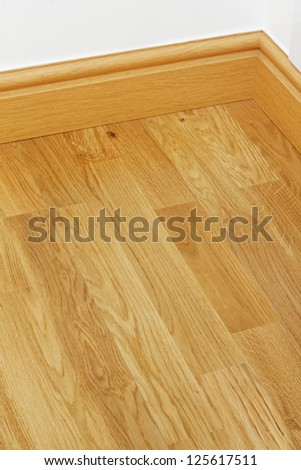 Close up showing some wood effect vinyl flooring and mdf imitation pine skirting boards in new build house - stock photo