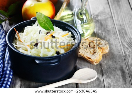 Close up Shredded Fresh Cabbage with Raisins on Black Cooking Pot with Herbs Top, placed on Wooden Table with Ladle, Bread and Other Ingredients. - stock photo