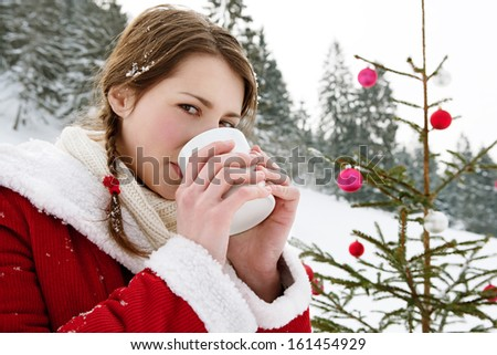 Close up side portrait of a beautiful woman in the snow mountains, celebrating christmas with a decorated xmas tree and holding a hot cup of tea or coffee beverage, outdoors. - stock photo