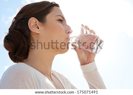 Close up side portrait of a beautiful young woman on holiday holding glass of pure mineral water and drinking against a sunny blue sky. Outdoors healthy lifestyle. - stock photo