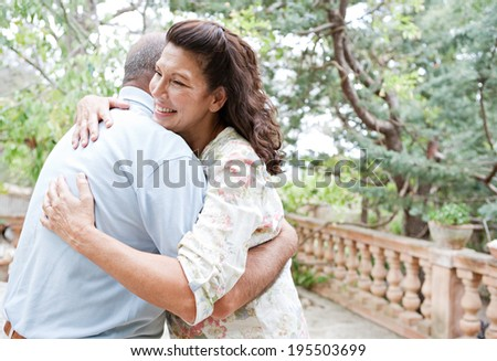 Close up side portrait of a healthy senior couple relaxing on holiday in a luxury garden, hugging each other and being loving. Mature people enjoying romance and retirement, outdoors lifestyle. - stock photo