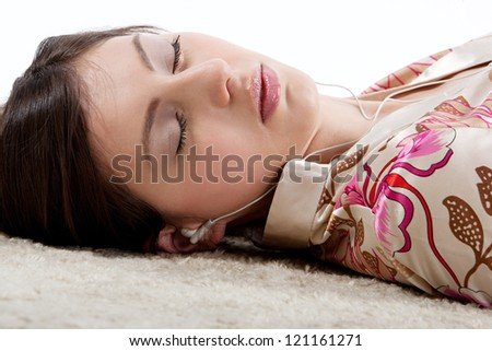 Close up side portrait of a young beautiful woman listening to music with her earphones while laying down on a furry carpet at home with her eyes closed. - stock photo