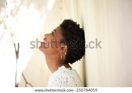 Close up side portrait of a young black woman smiling and looking up - stock photo