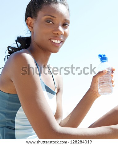 """Close up side portrait of an """"african american"""" woman sitting by the sea drinking mineral water and taking a break from doing sport, against a blue sky. - stock photo"""