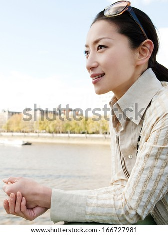 Close up side portrait of an attractive Japanese tourist woman leaning on the banister of a bridge in the city of London and contemplating the river Thames while on holiday with a blue sky. - stock photo