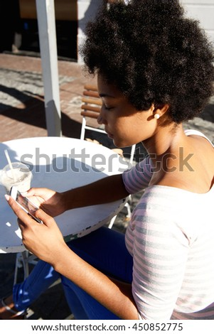Close up side portrait of beautiful woman sitting at outside cafe using phone