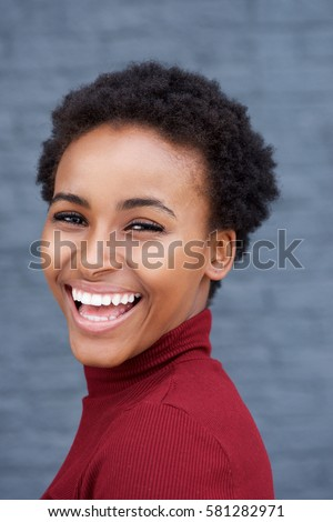 Close up side portrait of beautiful young black woman laughing