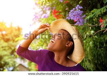 Close up side portrait of excited young african woman with hat standing outdoors - stock photo