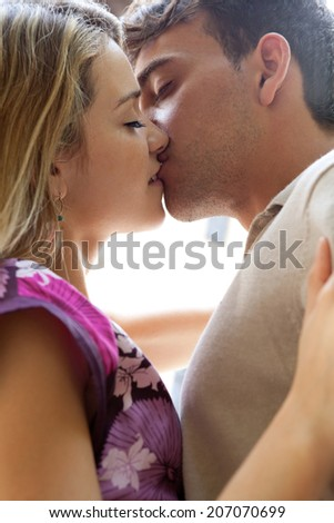 Close up side portrait view of a romantic young couple kissing each other with passion in a city street during a sunny day on holiday, outdoors. (People, Lifestyle, Romance) - stock photo