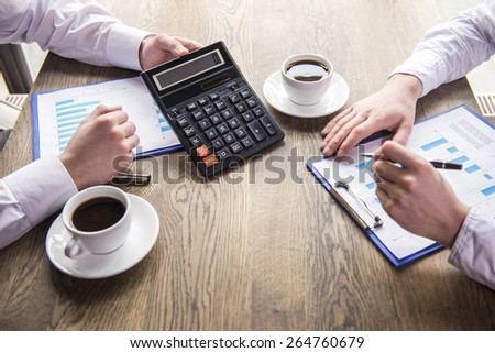 Close-up. Side view. Accounting. Financial analysis. Businessman analyzing graphs with cup of coffee in restaurant. - stock photo