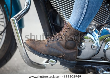 Close up, side view at female foot with protective brown boot on the stands of chopper motorbike with protective arcs