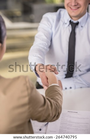 Close-up. Side view. Male candidate shaking hands with businesswoman at desk in office - stock photo