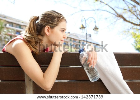 Close up side view of a young sports woman sitting down on a wooden bench in the city, relaxing from working out during a sunny morning and holding a bottle of mineral water. - stock photo