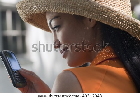 Close-up side view of a young woman wearing a sun hat and texting on her cell phone. Horizontal format. - stock photo