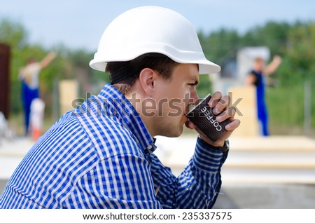 Close up side view of a young workman in a hardhat sipping coffee on a building site while the team continue work in the background - stock photo
