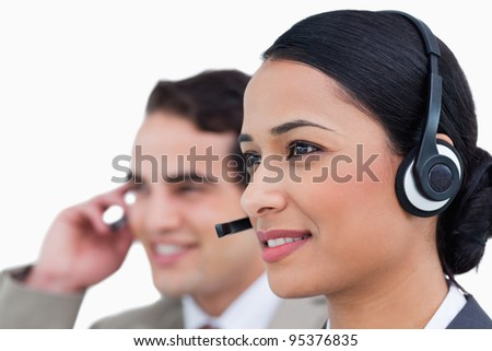 Close up side view of call center agents against a white background - stock photo