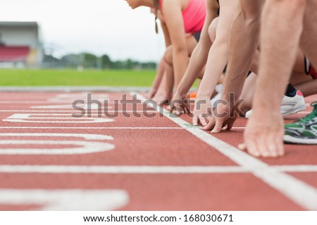 Close-up side view of cropped people ready to race on track field - stock photo