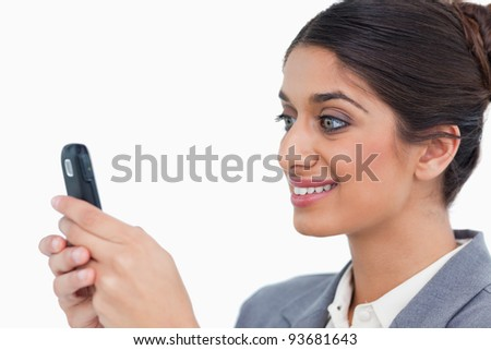 Close up side view of female entrepreneur reading text message against a white background